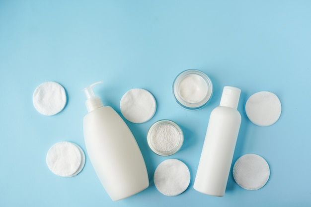 Bath products and cotton pads on blue background copy space Premium Photo