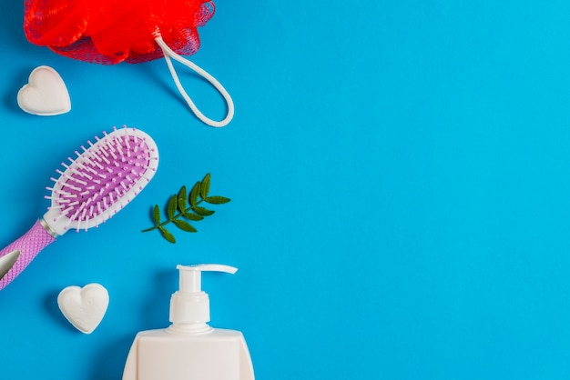 Bath puff; soap; dispenser bottle and leaves on blue background Free Photo