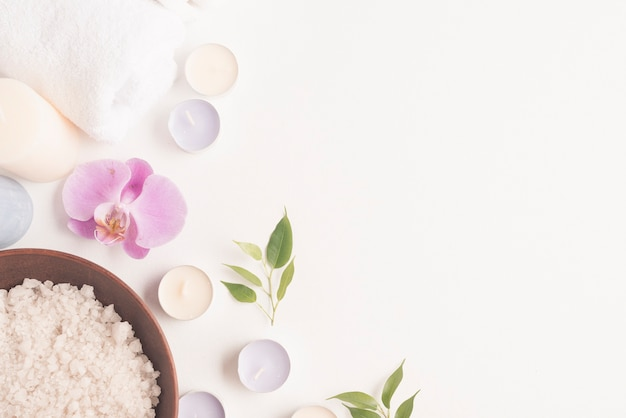 Bath salt with orchid flower and candles on white backdrop Free Photo
