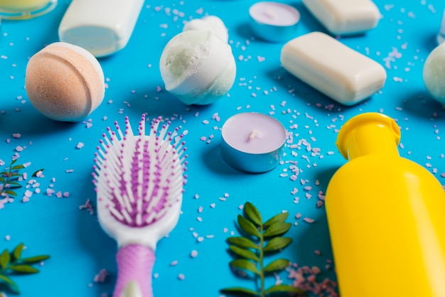 Bath soap with hairbrush and candle on blue background Free Photo