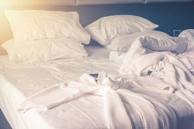 Bathrobe on bed in comfortable bedroom after wake up with messy bedding sheets and duvet with wrinkle messy in the bedroom Premium Photo