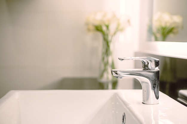 Bathroom interior luxury sink and faucet in toilet for washing hand with flower decoration Premium Photo