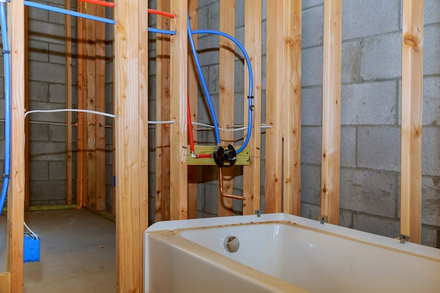 Bathroom remodel showing under floor plumbing work connecting installation of pipes for water for new buildings Premium Photo