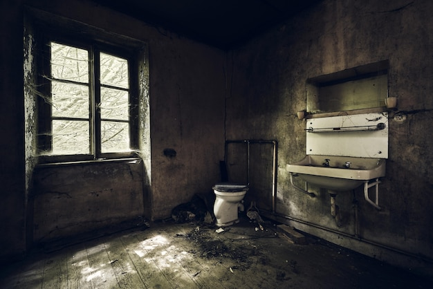버려진 건물의 조명 아래 흙으로 덮인 벽에 싱크대가있는 욕실 무료 사진