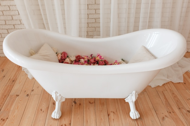Bathtub full of flowers in minimalistic interior with brick wall background Free Photo