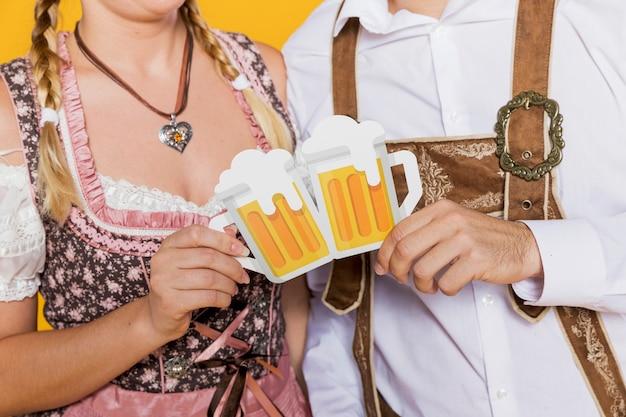 Bavarian couple holding paper beer mugs Free Photo