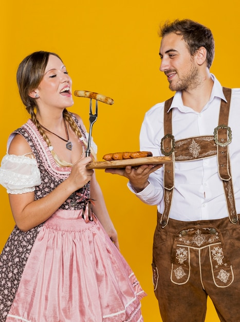 Bavarian couple trying german sausages Free Photo