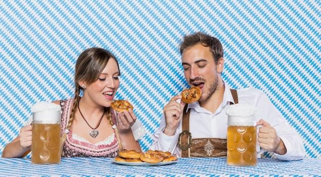 Bavarian friends tasting oktoberfest snacks Free Photo