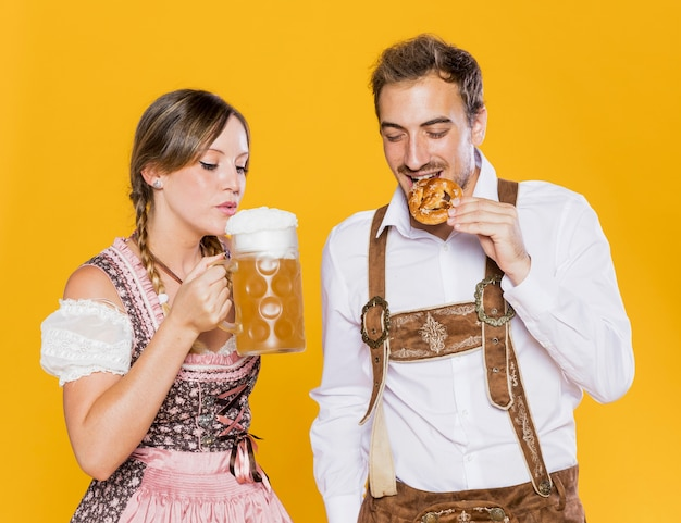 Bavarian friends trying oktoberfest snacks Free Photo