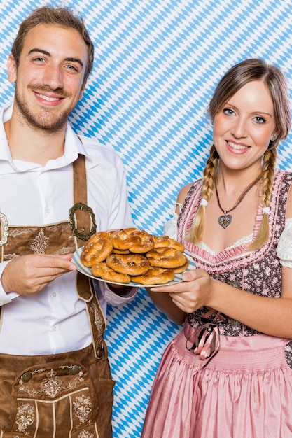Bavarian friends with pretzels smiling Free Photo