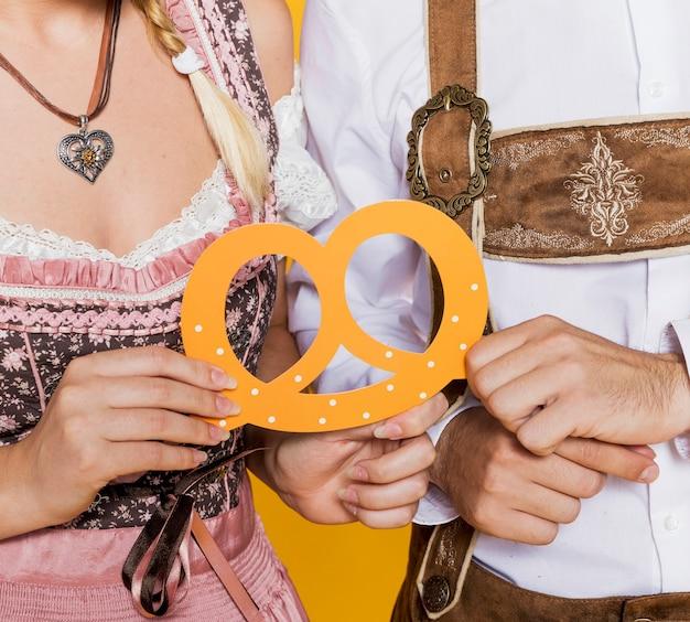 Bavarian man and woman holding pretzel Free Photo
