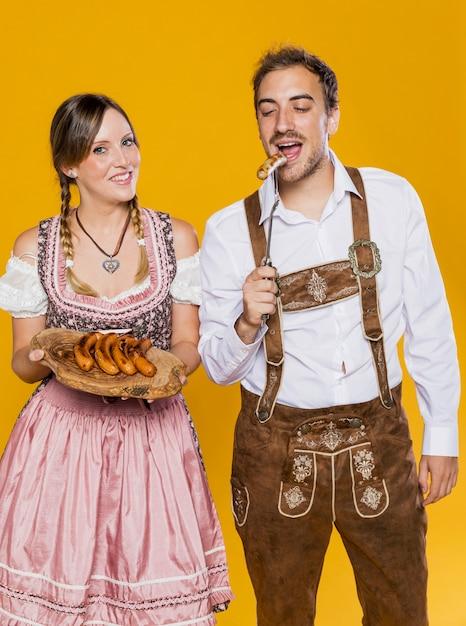 Bavarian man and woman trying bratwurst Free Photo