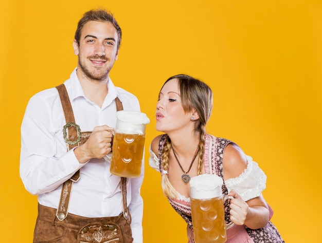 Bavarian young couple with beer mugs Free Photo