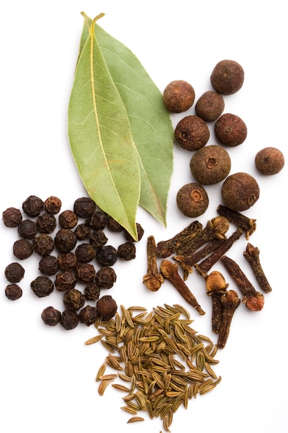 Bay leaves, cloves, caraway and black pepper on white