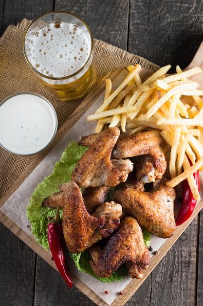 Bbq chicken wings with fries and beer. Premium Photo