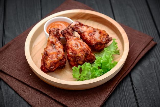 Куриные крылышки bbq с острым соусом чили на деревянной тарелке Premium Фотографии