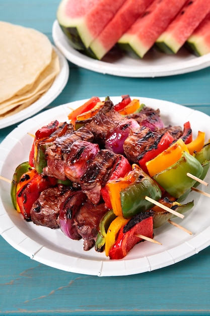 Bbq skewer with beef and vegetables on picnic table Free Photo