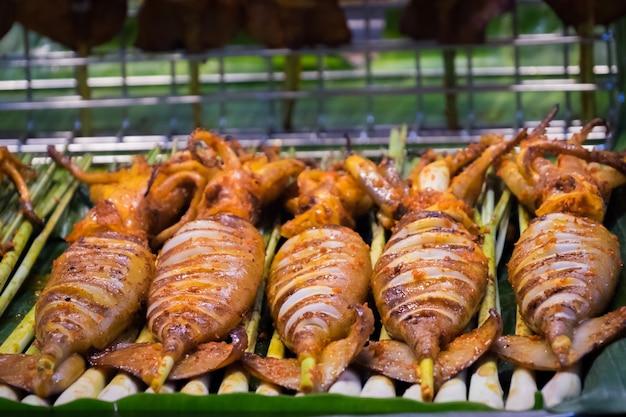 タイでグリルされたイカの通りの食べ物。 bbqイカのスティックに焼きイカの多く。 Premium写真