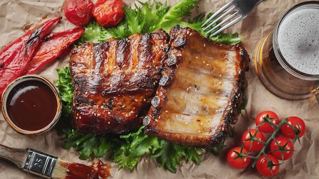 Крупный план свиных ребрышек зажарил с соусом bbq и карамелизованный в меде на бумаге. Premium Фотографии
