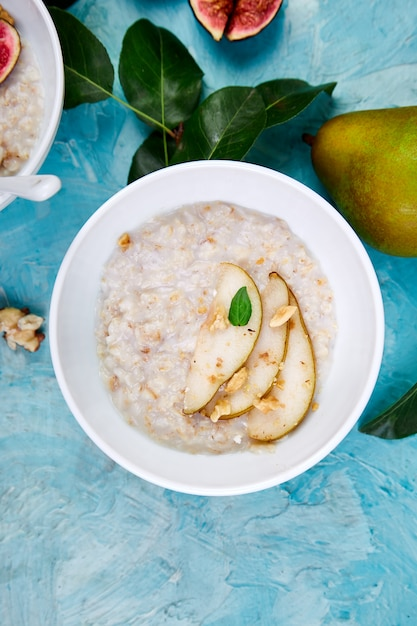 Bcosy,owl of porridge with pears slices and walnuts Premium Photo