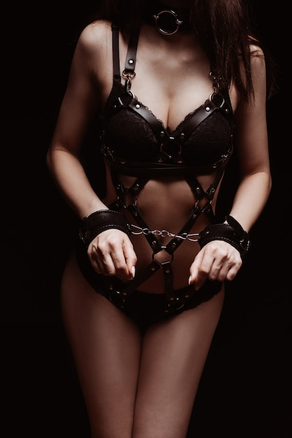 Bdsm. 수갑과 섹시한 검은 가죽 속옷 소녀 프리미엄 사진