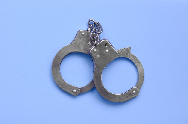 Bdsm and sex games concept. handcuffs on blue background Premium Photo