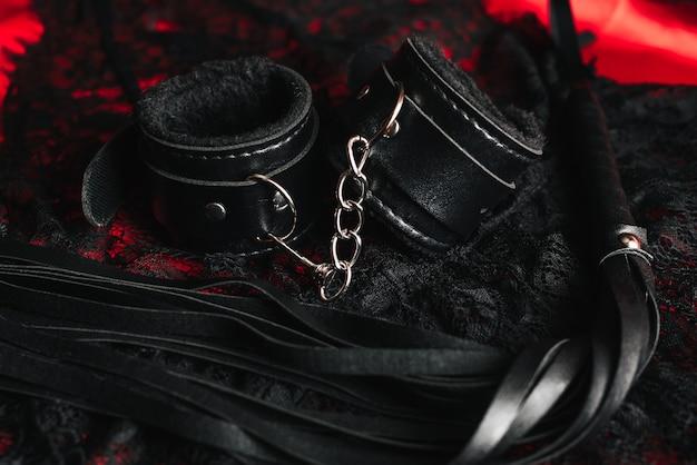 Bdsmロールプレイングセックスゲーム用の革の手錠と鞭 Premium写真