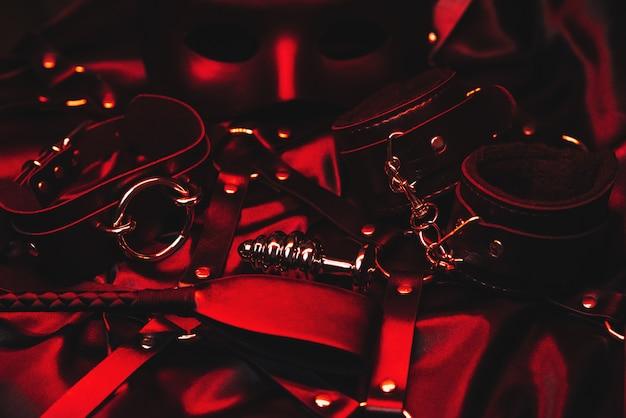 ロールプレイングのエロゲームのための金属製の肛門プラグ、革の手錠、鞭、ベルト、チョーカー、マスク。 bdsmセックスのおもちゃのセット Premium写真