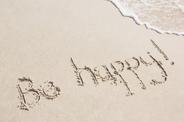 Be happy written on sand - Freepik