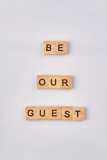 Будь нашим гостем деревянные слова. изолированные на белом фоне. Premium Фотографии