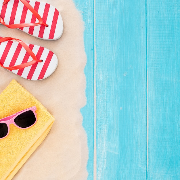 Beach accessories on blue plank and sand - summer holiday background Free Photo