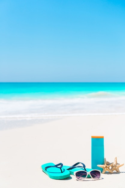 Beach accessories needed for sun protection. suncream bottles, goggles, flip flops, starfish on white sand beach with ocean views Premium Photo