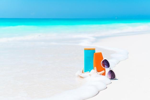 Beach accessories needed for sun protection. suncream bottles, sunglasses, starfish on white sand beach Premium Photo