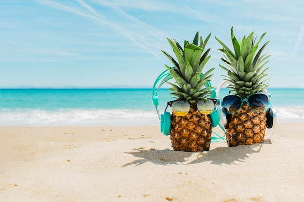 Beach background with cool pineapples wearing headphones Free Photo