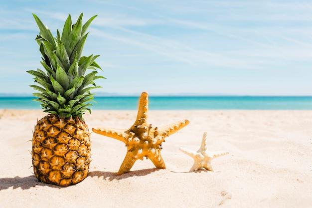 Beach background with pineapple and starfish Free Photo