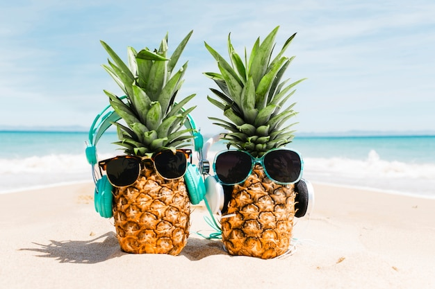 Beach background with pineapples wearing sunglasses Free Photo