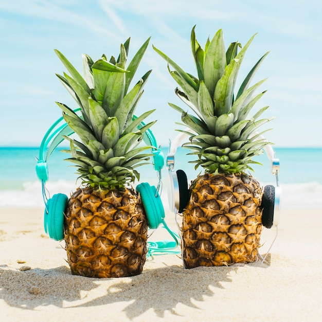 Beach background with two pineapples wearing headphones Free Photo
