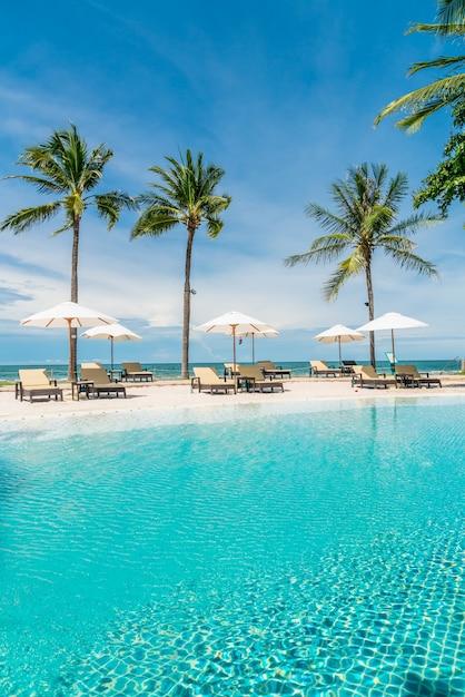 海のビーチ、休日や休暇の概念を持つホテルリゾートのプールの周りのビーチチェア Premium写真