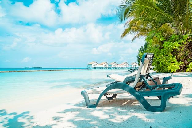 熱帯のモルディブリゾートホテルの島と海とビーチチェア Premium写真