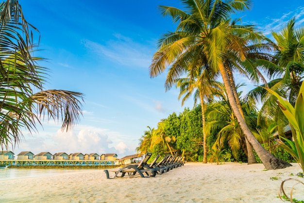 Beach chairs in maldives island with water villas at the sunrise time . Premium Photo