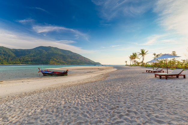 Beach chairs, umbrella and palms on the beautiful beach for holidays and relaxation at koh lipe island, thailand Premium Photo