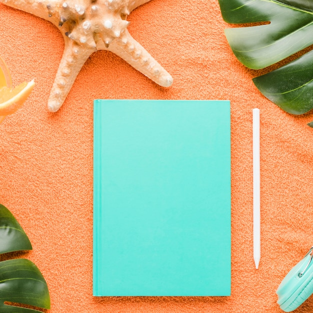 Beach composition with notebook on colored background Free Photo