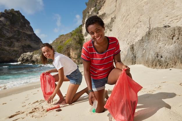 Пляжная среда и концепция уборки мусора. два веселых волонтера собирают мусор на берегу Бесплатные Фотографии