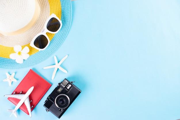 Пляжная шляпа, солнцезащитные очки, камера, паспорт и флип-флоп на светло-синем фоне. лето или отпуск. Premium Фотографии