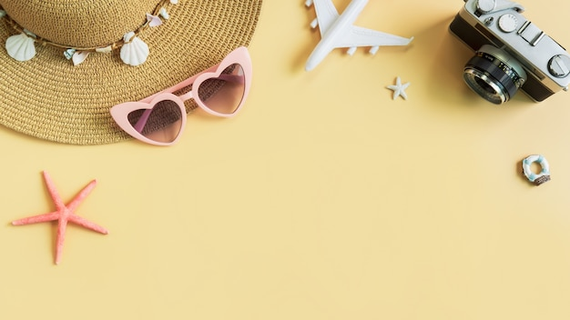 Beach hat with camera and travel items on yellow background, summer vacation concept Premium Photo