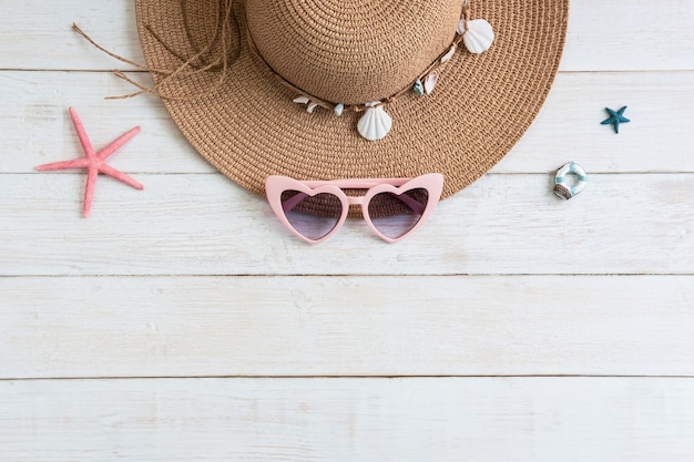 Beach hat with travel items on white wooden background, summer vacation concept Premium Photo