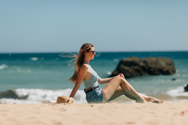 Beach holidays woman back view enjoying summer sun sitting in sand looking happy at copy space. beautiful young model Free Photo