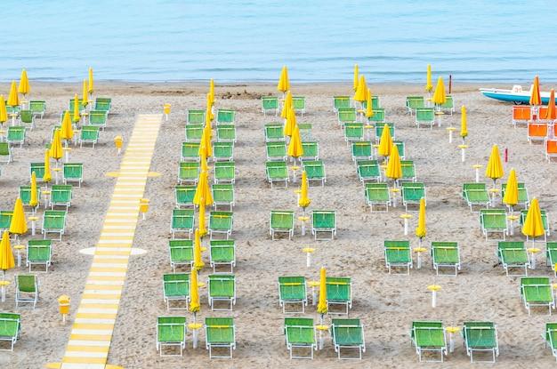 이탈리아 해안선에 노란색 우산과 녹색 선베드가있는 해변 라운지 공간. 프리미엄 사진