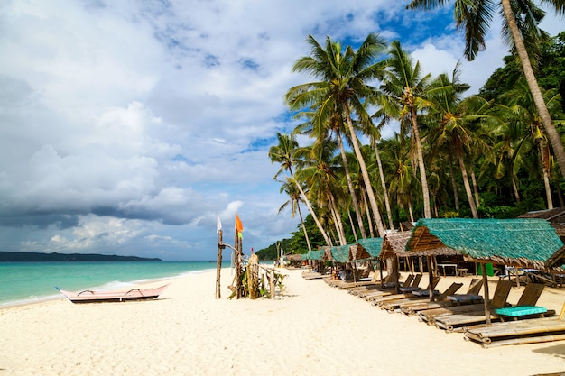 Beach loungers without people in sunny tropical beach on boracay island, phillipines Premium Photo