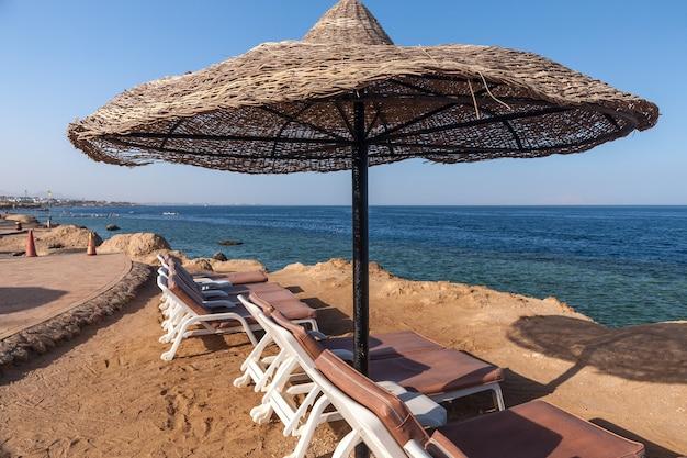 La spiaggia dell'hotel di lusso, sharm el sheikh, egitto. ombrello contro il cielo blu Foto Gratuite